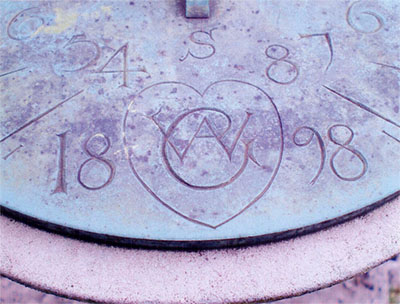Voysey sundial showing the letters AWC in a heart shape